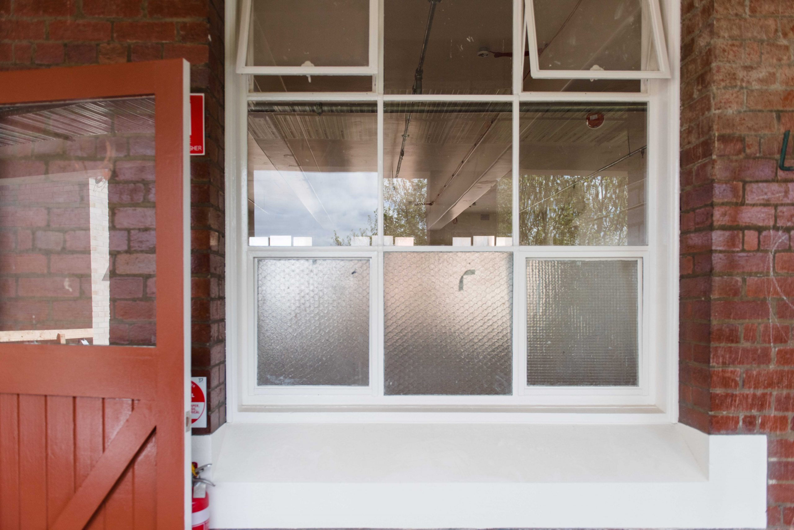 White framed windows with an opened maroon-coloured door