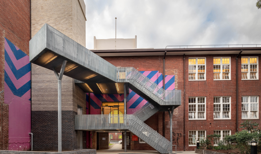A brick 3-storey building with an external steel staircase and a blue and pink mural