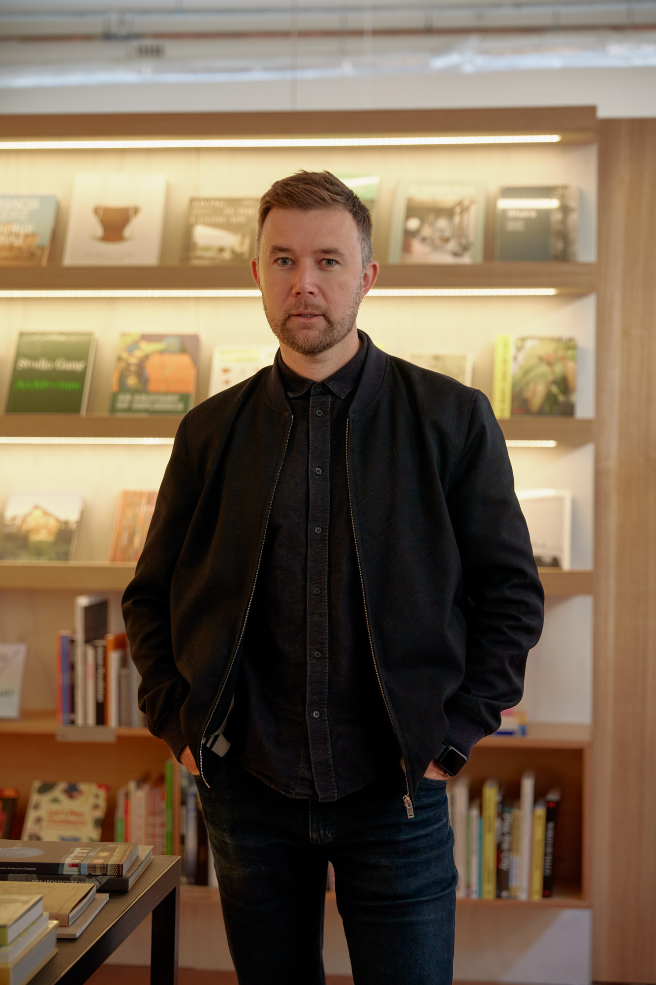 Matieu Ward, publisher and bookseller stands in the Bookshop by Uro tenancy space