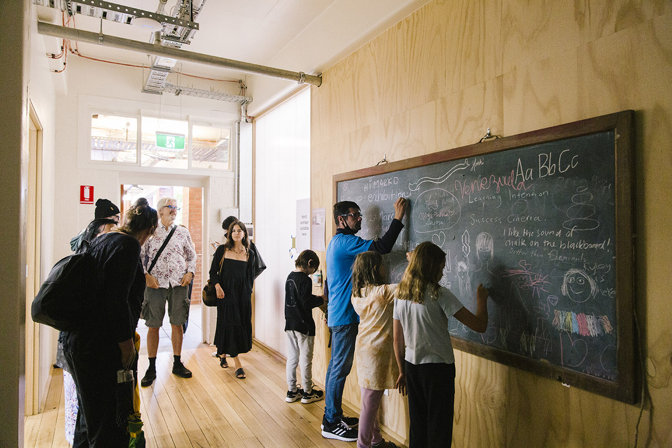 Visitors to Collingwood Yards draw on a chalkboard outside the studio